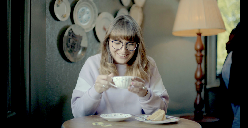 a person with long brown hair drinking a cup of tea and laughing